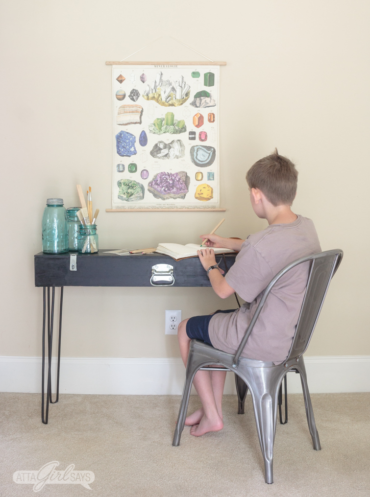Photo of a boy in a brown T-shirt sitting at a black hairpin leg desk. The boy is drawing. The desk is decorated with three old blue mason jars, and a poster of gemstones hangs above the desk.