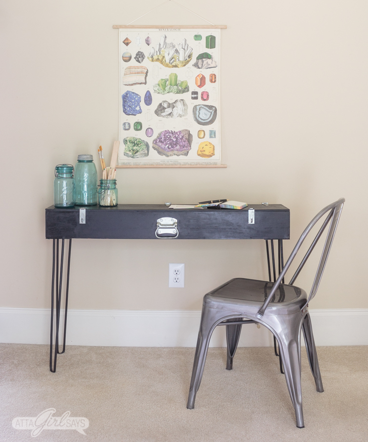 Photo of a black DIY hairpin leg desk against a beige wall. A gunmetal bistro chair sits in front of the desk. A trio of blue mason jars, art supplies and a notebook sit on top of the desk. There's a scientific poster of gemstones and minerals hanging above the desk.