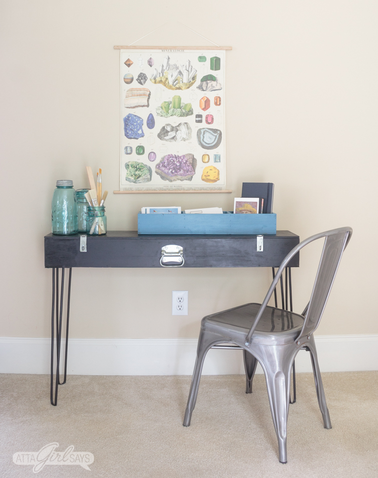 A black hairpin leg desk with art supplies on top of it.
