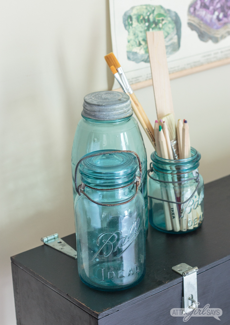 Three vintage blue mason jars, filled with pencils and other art supplies, on top of a small black writing desk.