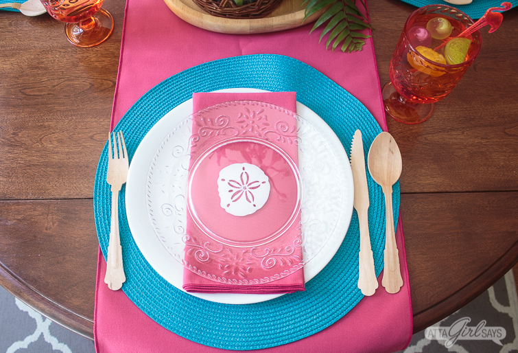 Dinner place setting featuring a clear plate with a sand dollar design atop a white dinner plate, aqua blue woven placemat and a hot pink table runner.