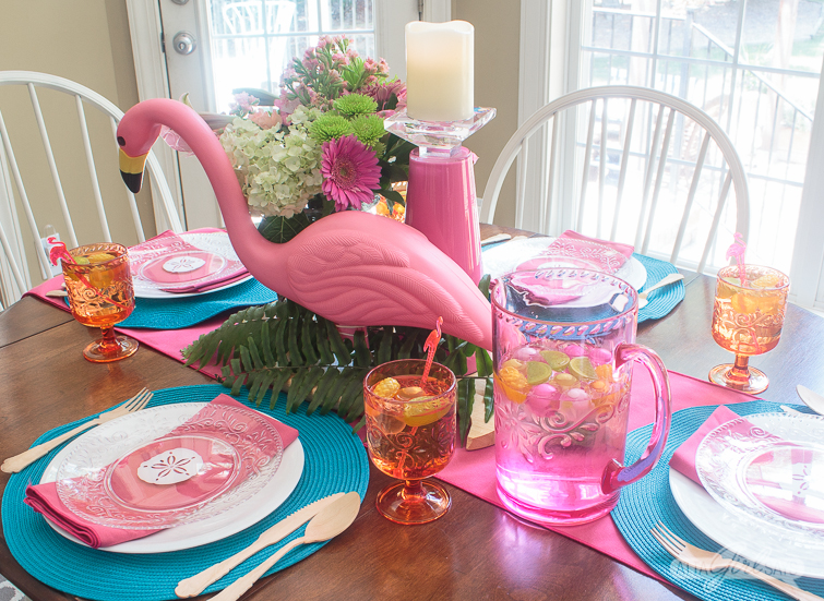 Dinner table set with bright pink, blue and orange melamine dishes, glasses and flamingo accents