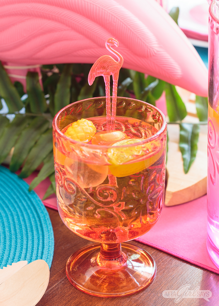 An orange plastic water goblet filled with colorful plastic fruit ice cubes and a flamingo swizzle stick.