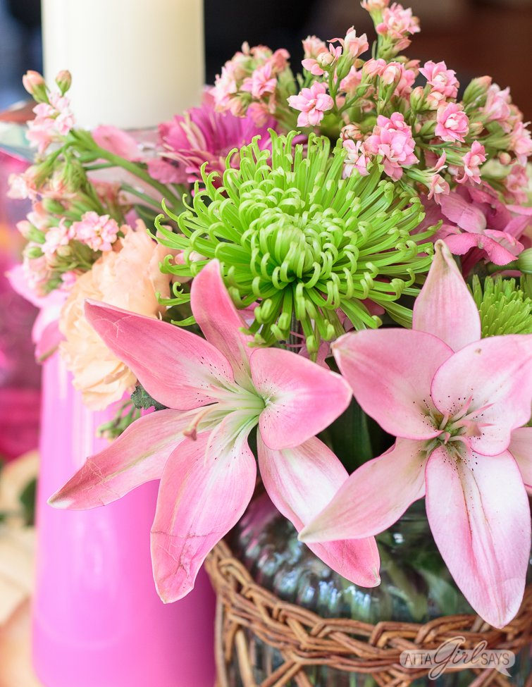 Closeup of pink lilies and green flowers in a floral arrangement.