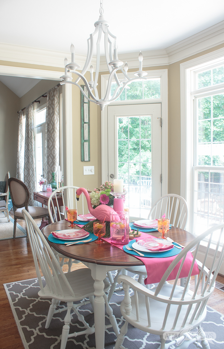 A kitchen table set for dinner, decorated with pink flamingo party supplies and pink and aqua blue linens.