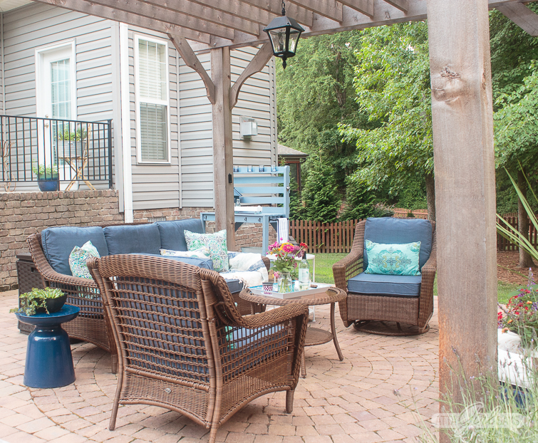 Outdoor patio area with a pergola, a solar chandelier and an outdoor wicker seating set with sofa, glider and chair.