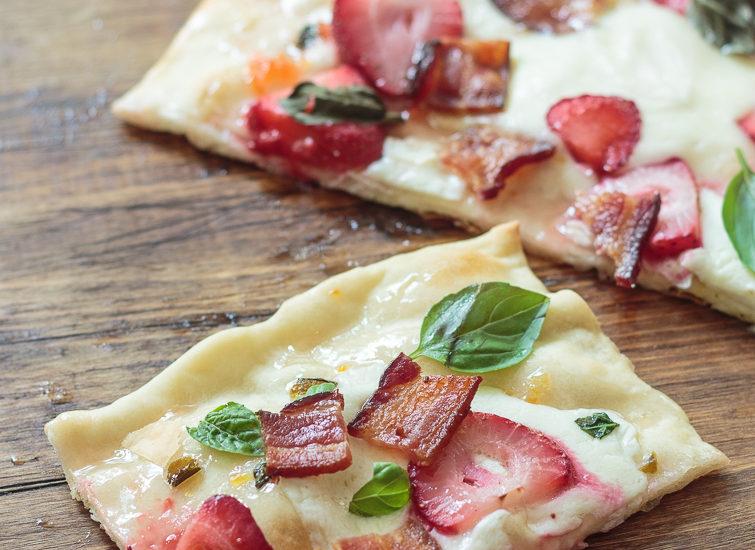Overhead view of strawberry bacon flatbread pizza with fresh mozzarella and basil