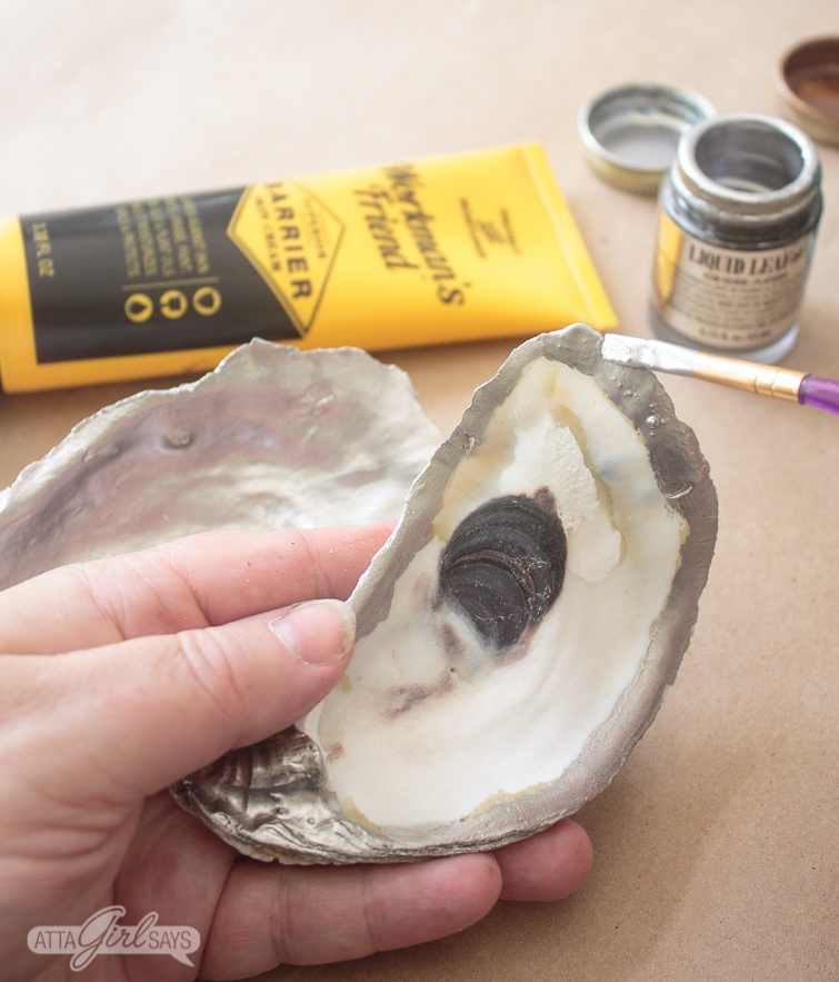 closeup of a woman's hand working on a oyster shell craft. She is painting silver liquid leaf around the inner edge of the shell using a small paintbrush.