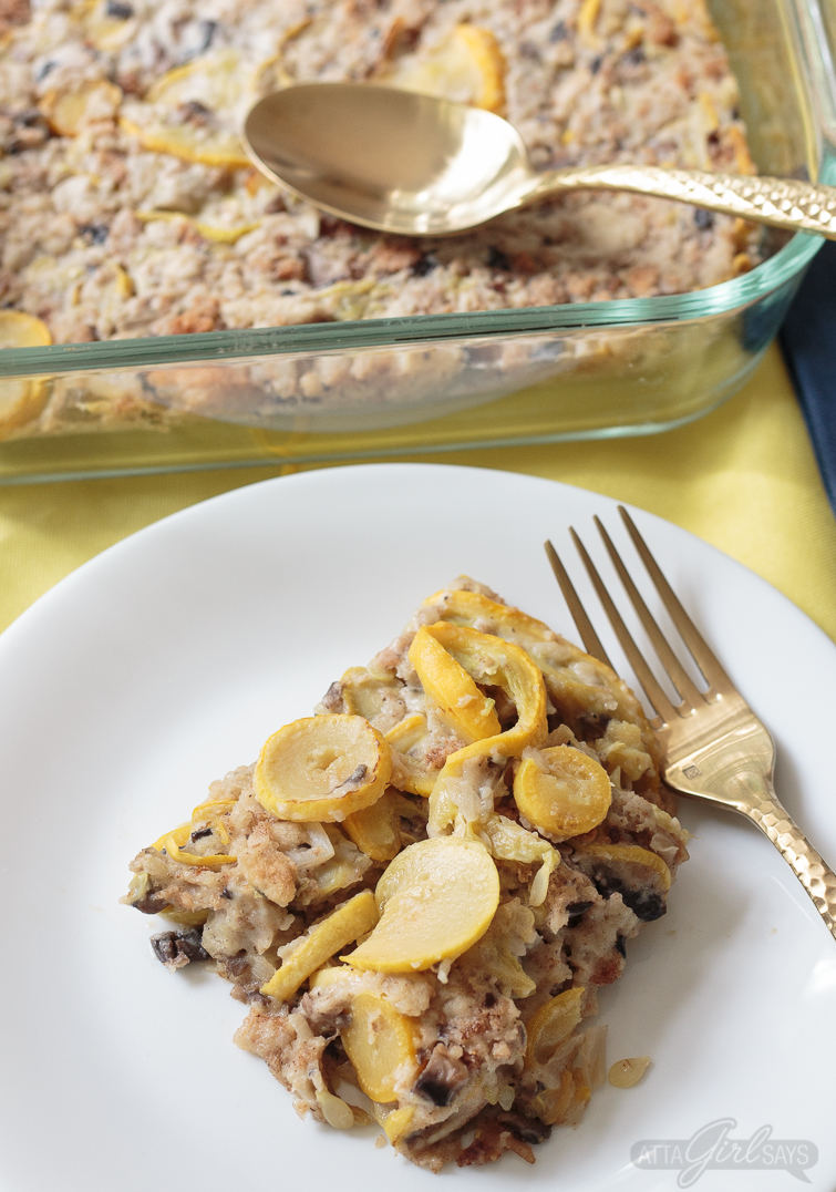 Overhead photo of a serving of yellow squash casserole with stuffing on a white plate with a casserole dish in the background