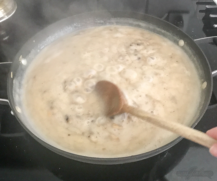 homemade cream of mushroom soup bubbling in a saute pan