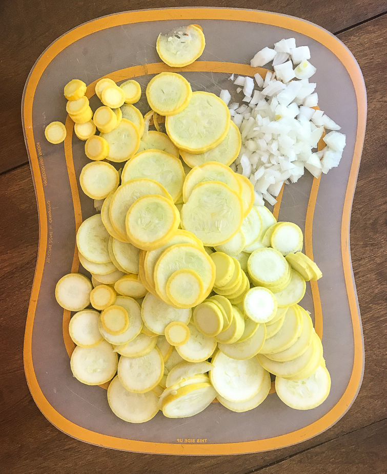 Cutting board with slices of yellow squash and chopped onion for a stuffing squash casserole