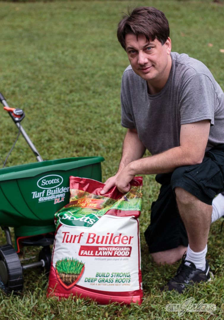 man kneeling in a yard beside a bag of Scott's Turf Builder Fall Lawn Food and a broadcast grass seed spreader