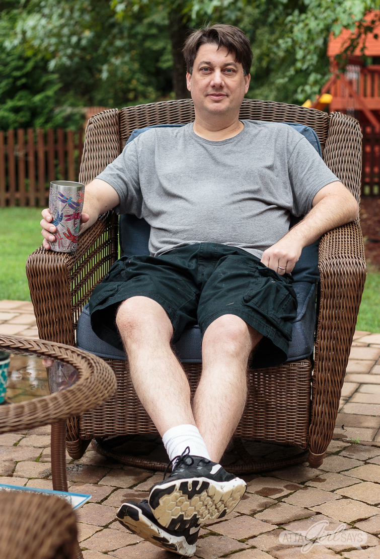 Man wearing a gray t-shirt and black pants, sitting in an outdoor wicker patio rocker, holding a cup
