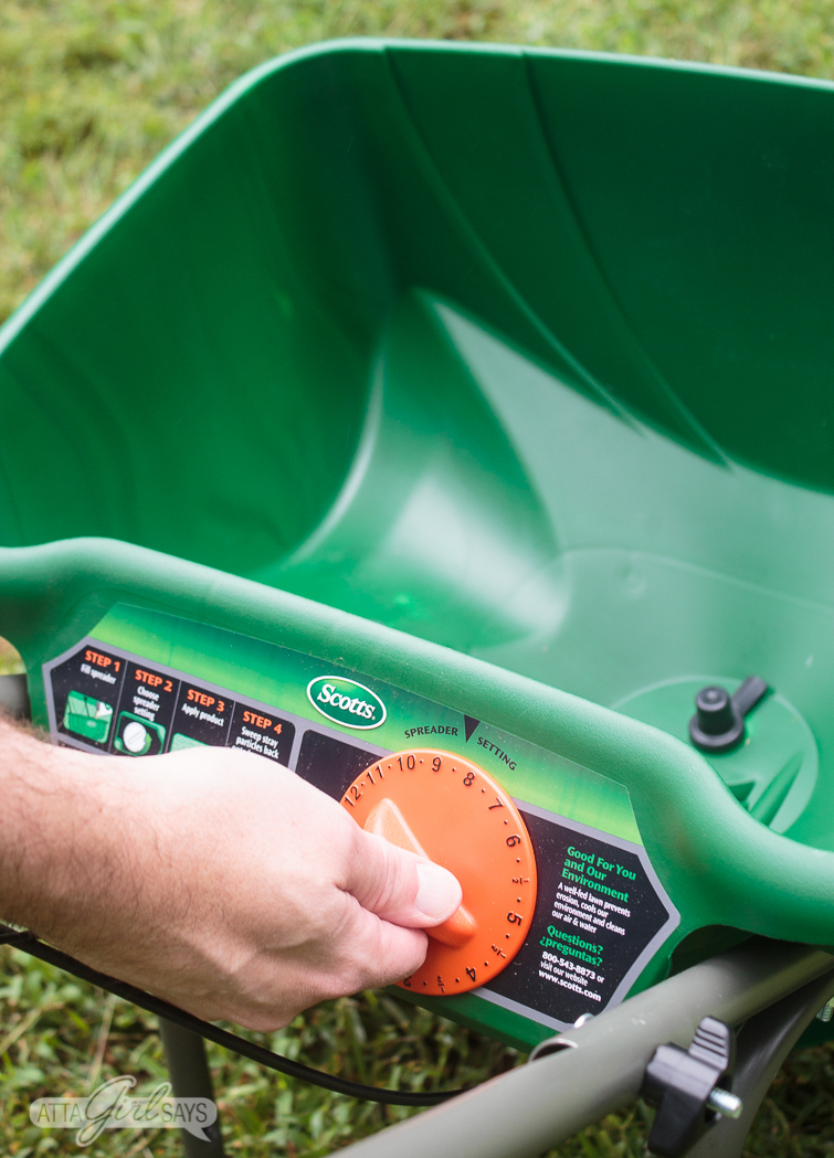 man's hand adjusting the dial on a broadcast grass seed spreader