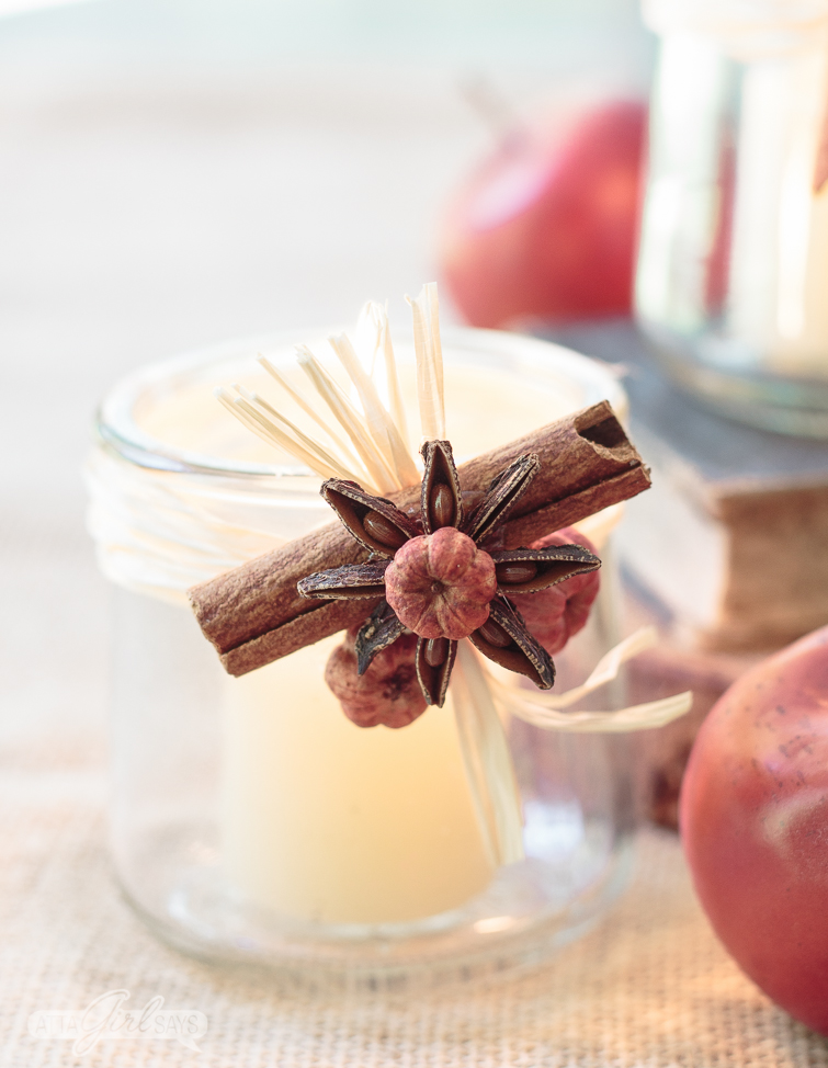 tealight candle holder decorated with cinnamon sticks, anise star and seed pods with a stack of old books and small red apples in the background