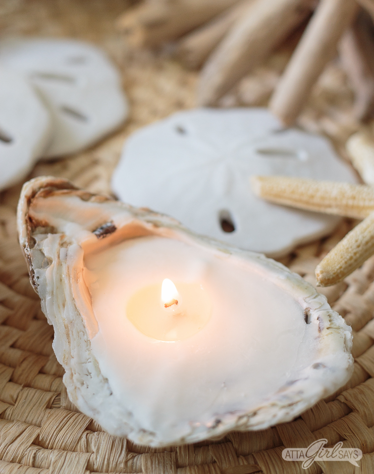 homemade oyster seashell candle burning on a seagrass mat with sand dollrs and starfish in the background