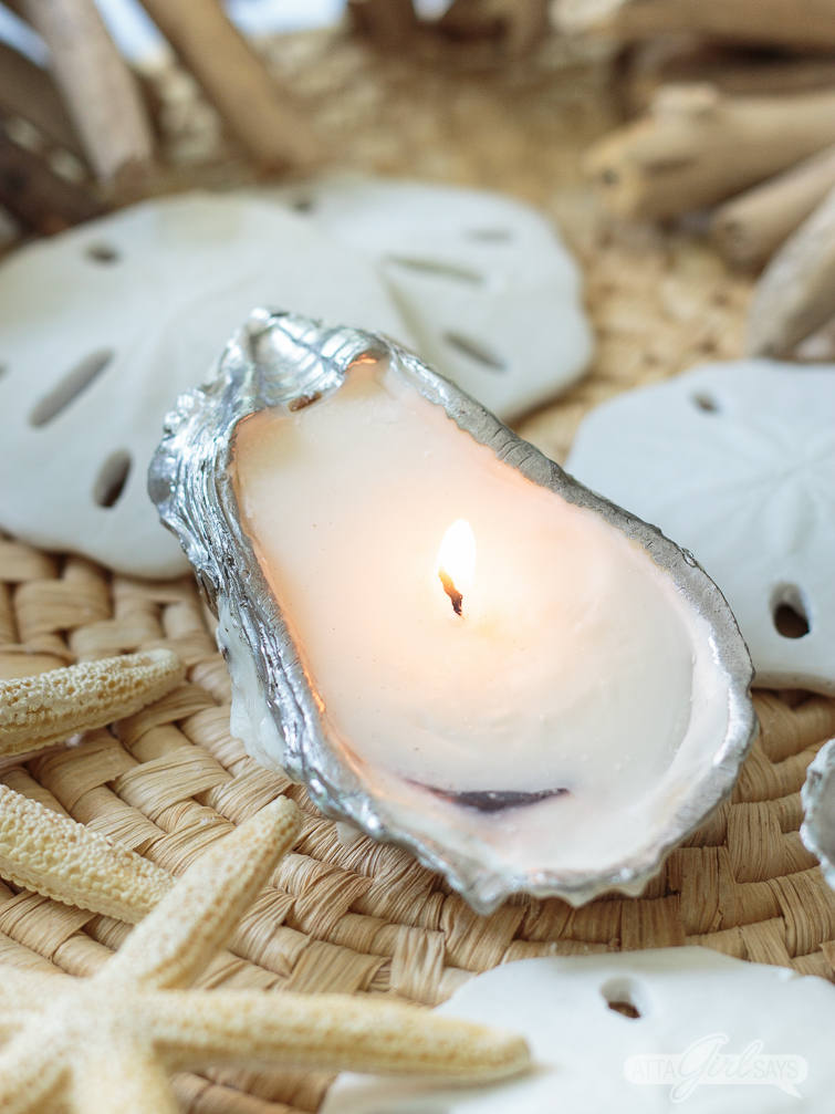 Homemade candle in an oyster shell sitting on a woven seagrass mat alongside sand dollars and starfish. The oyster shell craft has a silver leafed edged