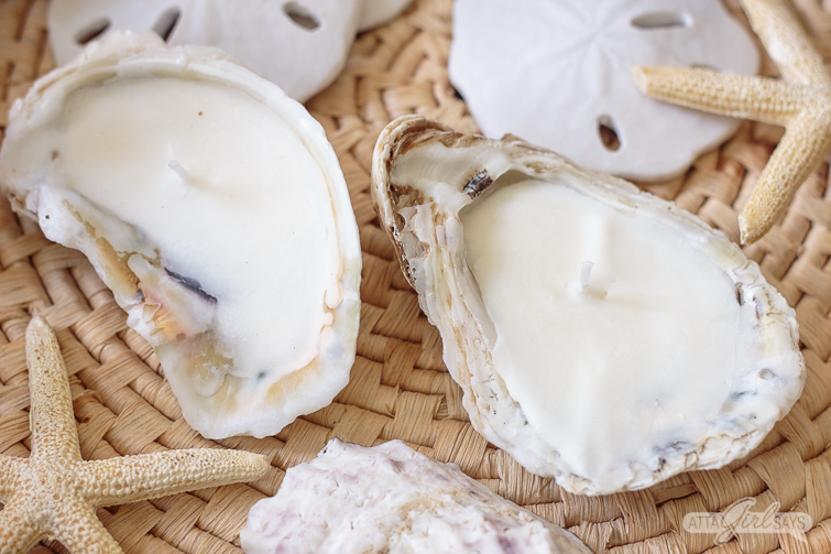 Homemade oyster sea shell candles on a woven seagrass mat