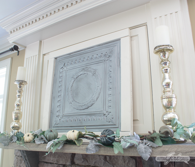 silver tin ceiling panel on a fireplace mantel, decorated with a silvery green fall garland and tall mercury glass candlesticks