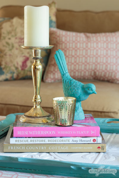stack of decorating books on a wooden tray made from a faux tin ceiling tile and an aqua frame