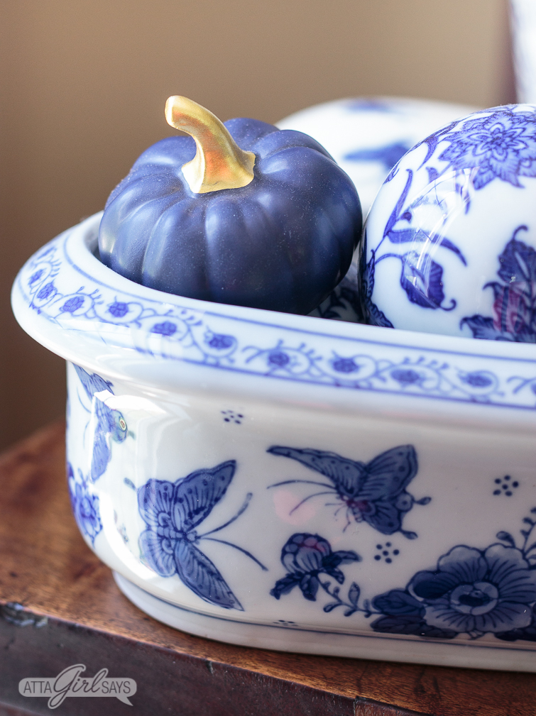 blue ceramic pumpkin and blue and white chinoiserie balls in a blue and white butterfly planter