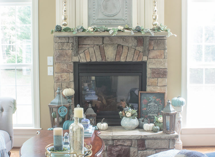 family room decorated in blue and gray with a stone fireplace flanked by two windows