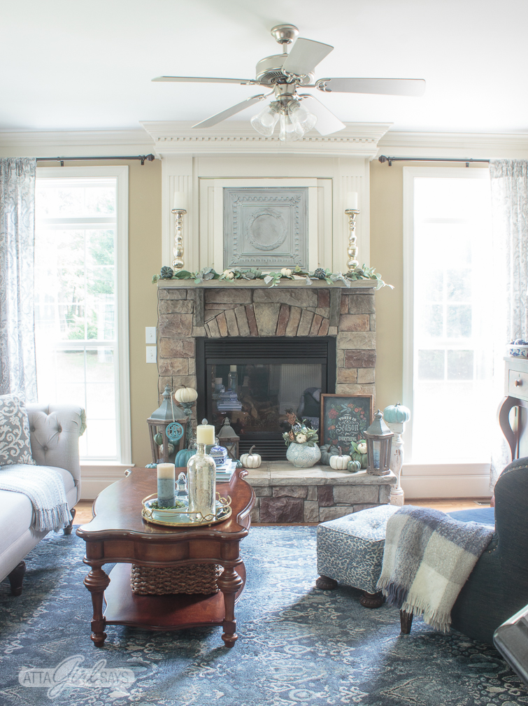 mantel decor ideas: family room decorated in blue and gray with a stone fireplace flanked by two windows