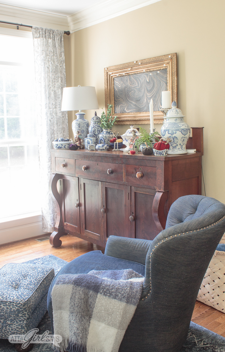 denim blue club chair with a blue leopard print ottoman sitting beside an empire style buffet decorated with blue and white chinoiserie pottery