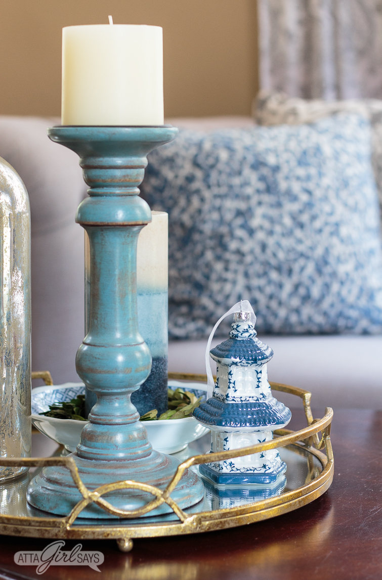 gold mirrored tray on a coffee table with a blue candlestick and a Chinese pagoda ornament sitting on it