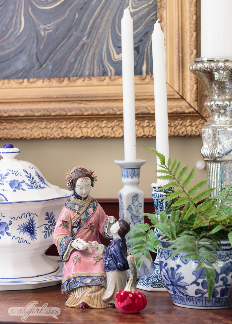chinese figurine and blue and white chinoiserie pottery on a sideboard