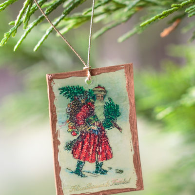 clear plastic Santa claus Shrinky Dinks Christmas ornament hanging on a tree branch