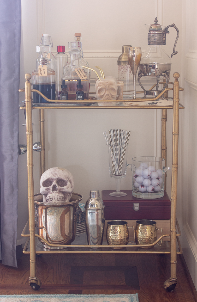 gold bamboo bar cart decorated for Halloween with glass decanters, bitters, a skull in a champagne bucket and eyeballs in a glass bowl