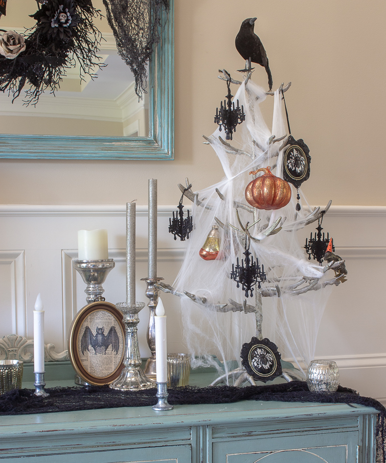 Halloween tree draped with spiderwebs and orange and black ornaments with a crow on top