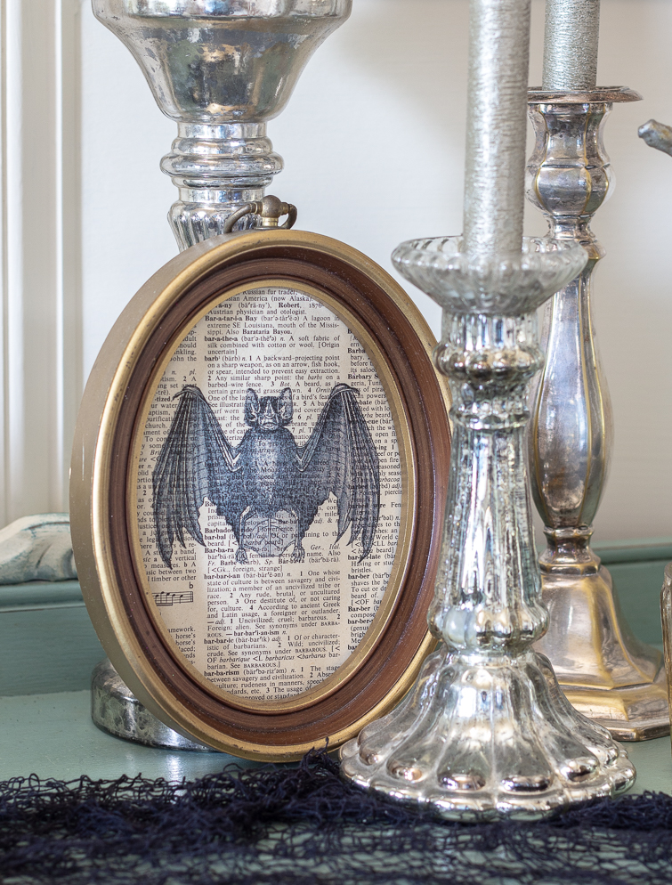 mercury glass candlesticks and dictionary page artwork printed with the image of a vampire bat