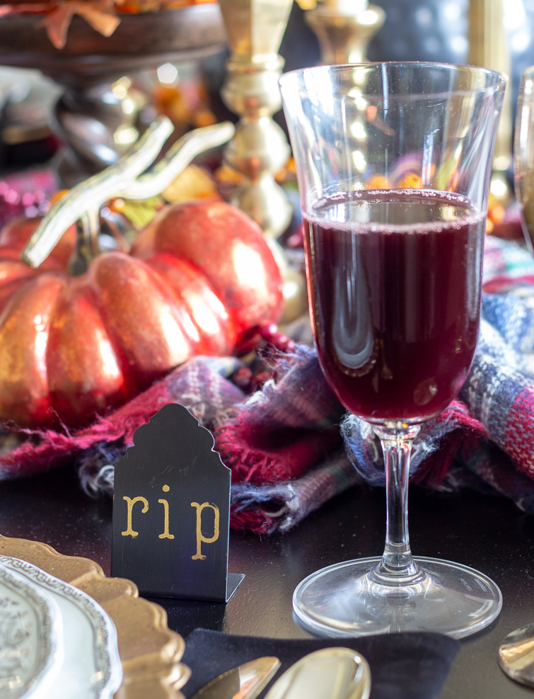 wine goblet filled with blood red juice as part of Halloween table decorations