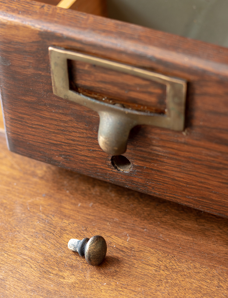 closeup of a card catalog drawer with a missing knob