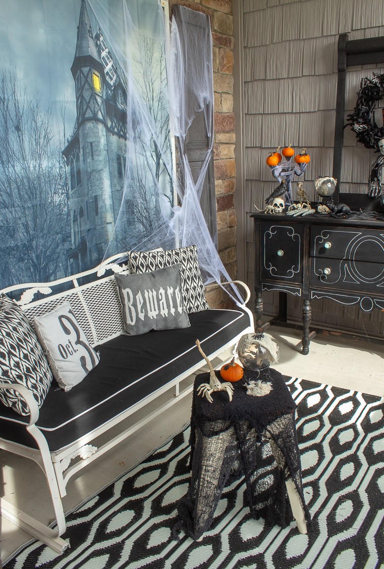 haunted house shower curtain hanging behind a bench on a Halloween front porch