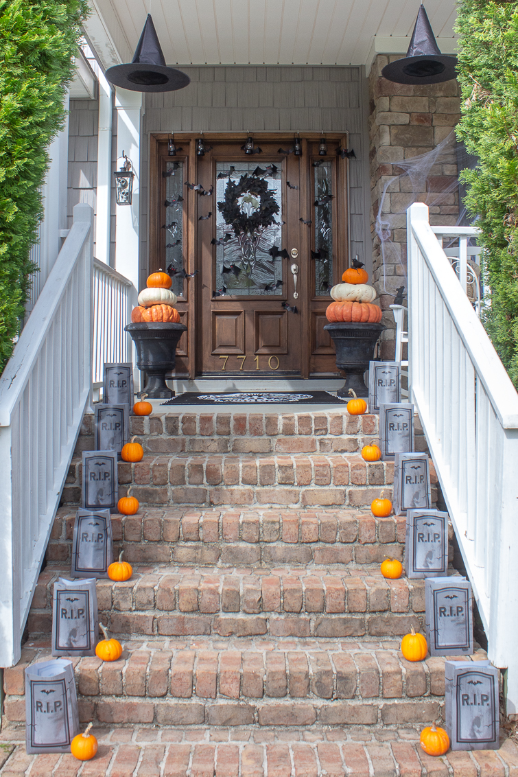porch stairs lined with min pumpkins and Halloween luminarias with two pumpkin topiaries in urns flanking a front door covered with bats