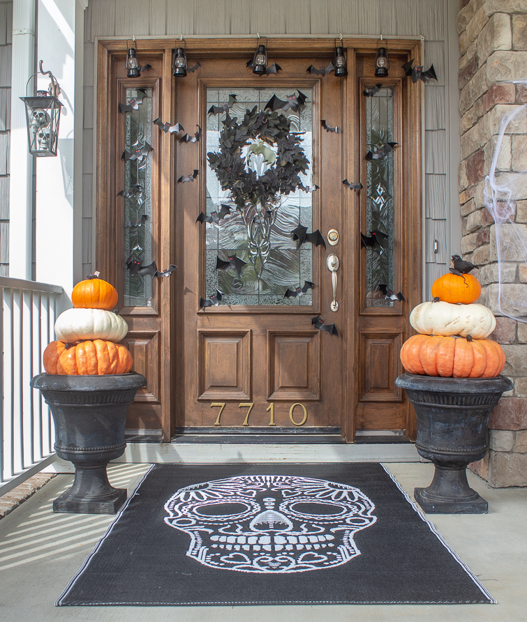 Halloween entryway decorated with a black skeleton rug, a pair of Cinderella pumpkin topiairies in urns and black bats and a black wreath on a wooden stained door