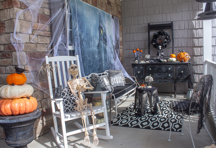 Halloween skeleton on a spooky front porch decorated in black, white and orange