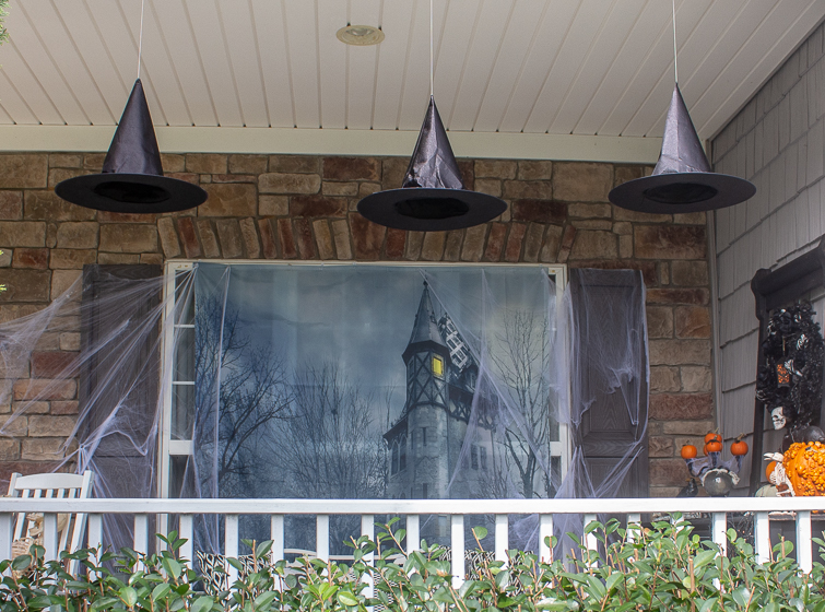 haunted house backdrop hanging on a window on a Halloween front porch with witch hats floating above it