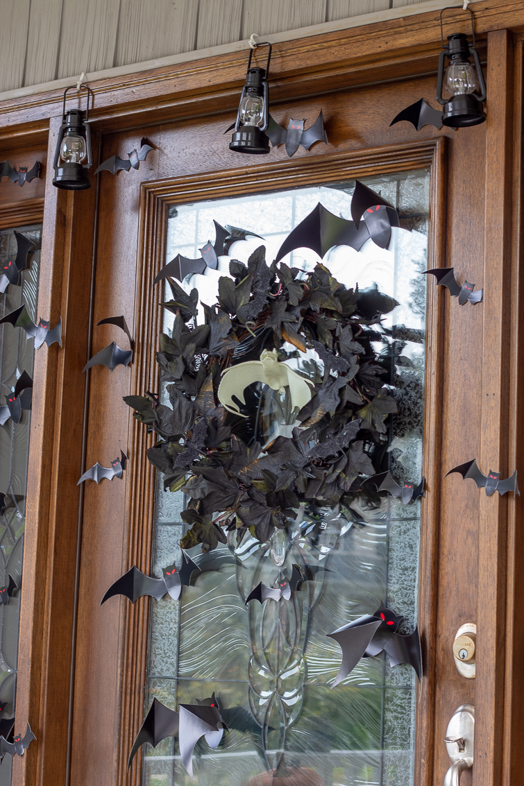 black maple leaf wreath and paper bats on a front door