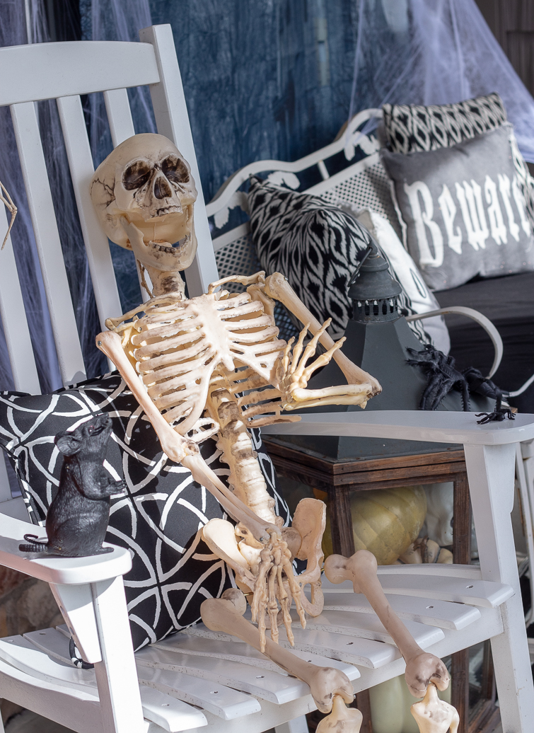 plastic skeleton in a rocking chair on a Halloween front porch decorated in black, white and orange