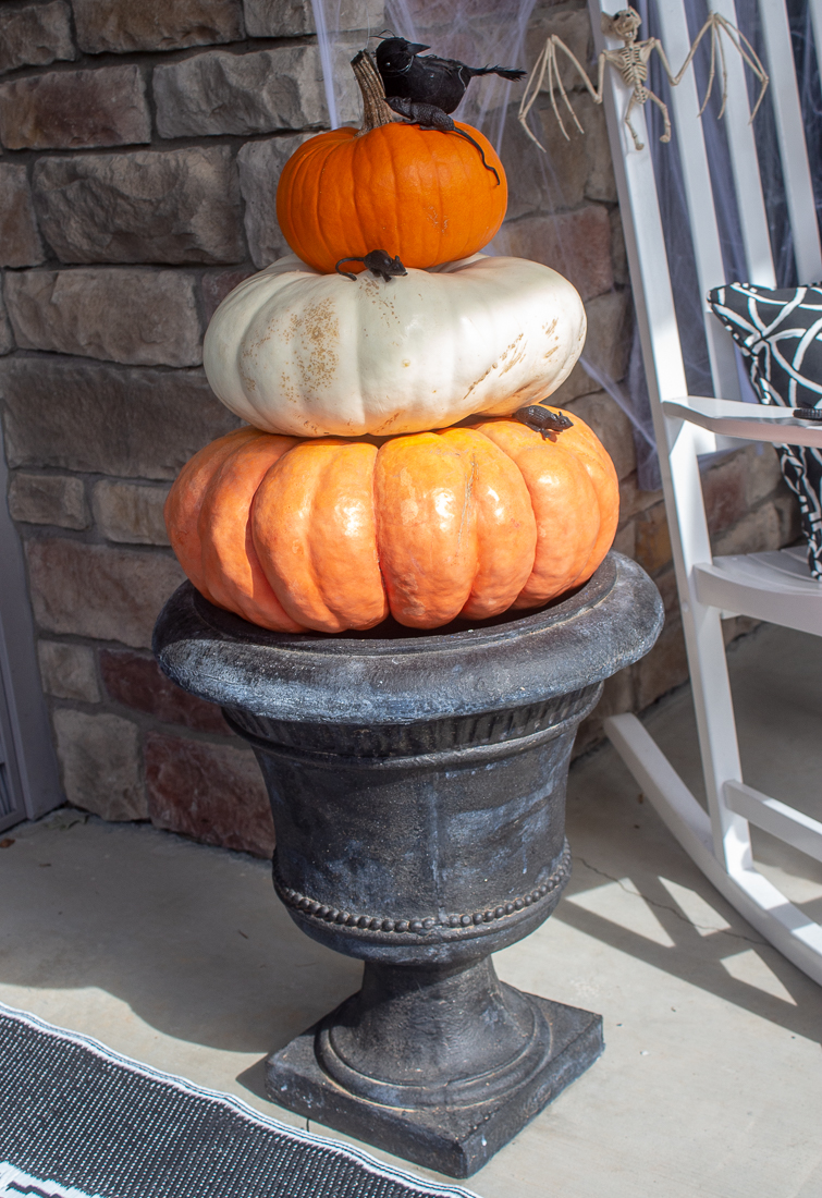 orange and white Cinderella pumpkins stacked in a black urn