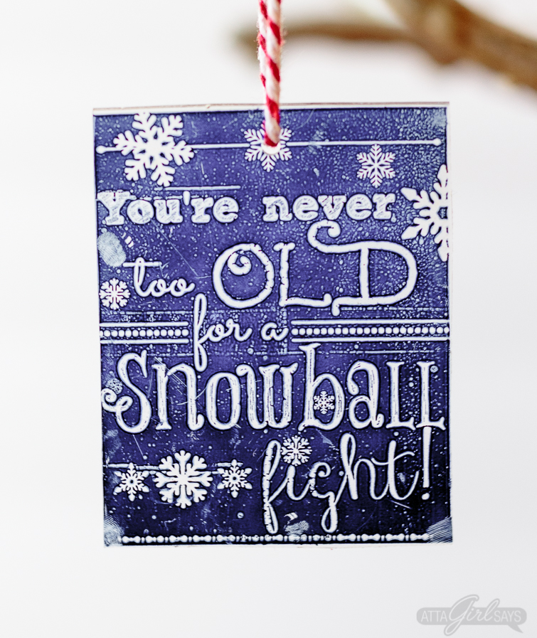 "Shrinky Dinks Christmas ornament on a chalkboard background with the saying, ""you're never too old for a snowball fight"""