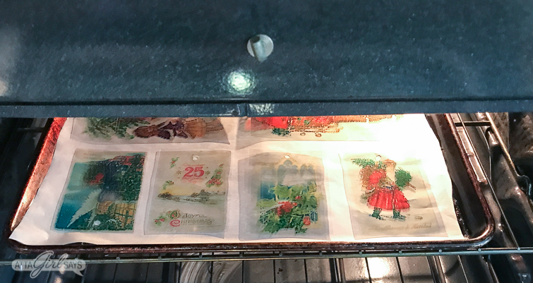 Vintage Christmas postcard Shrinky Dinks Christmas ornaments in the oven on a parchment lined baking sheet