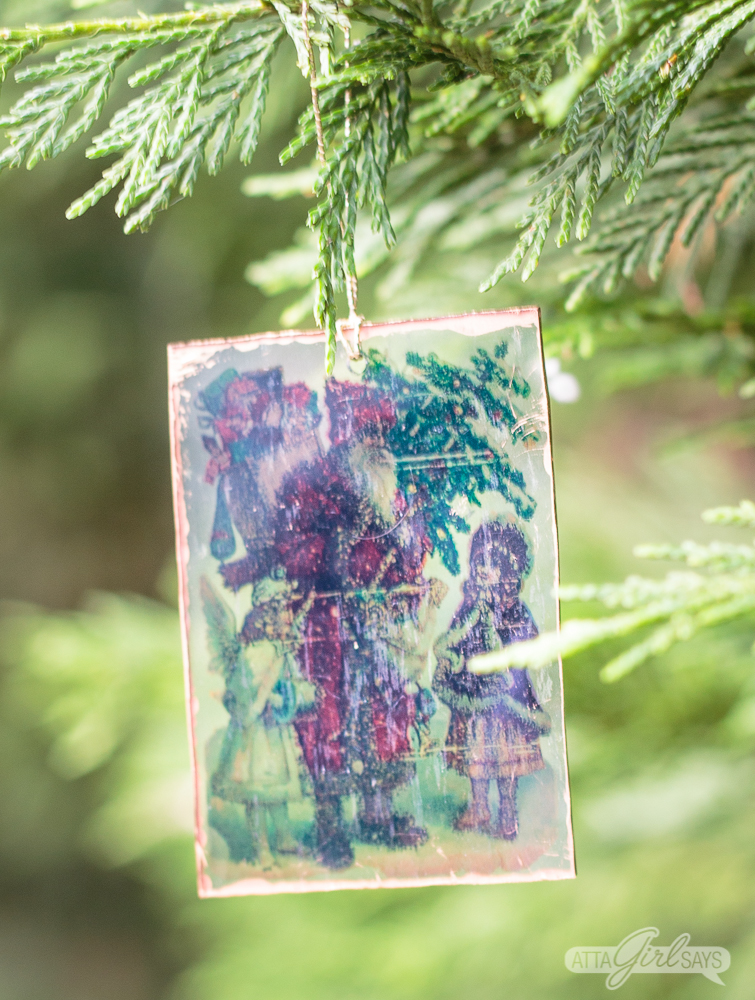 clear plastic Santa Claus with kids Shrinky Dinks Christmas ornament hanging on a tree branch