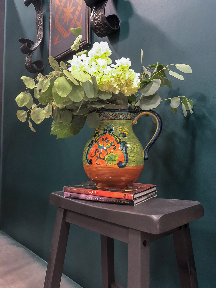 eucalyptus and white hydrangeas in an Italian pitch on top of a dark gray stool