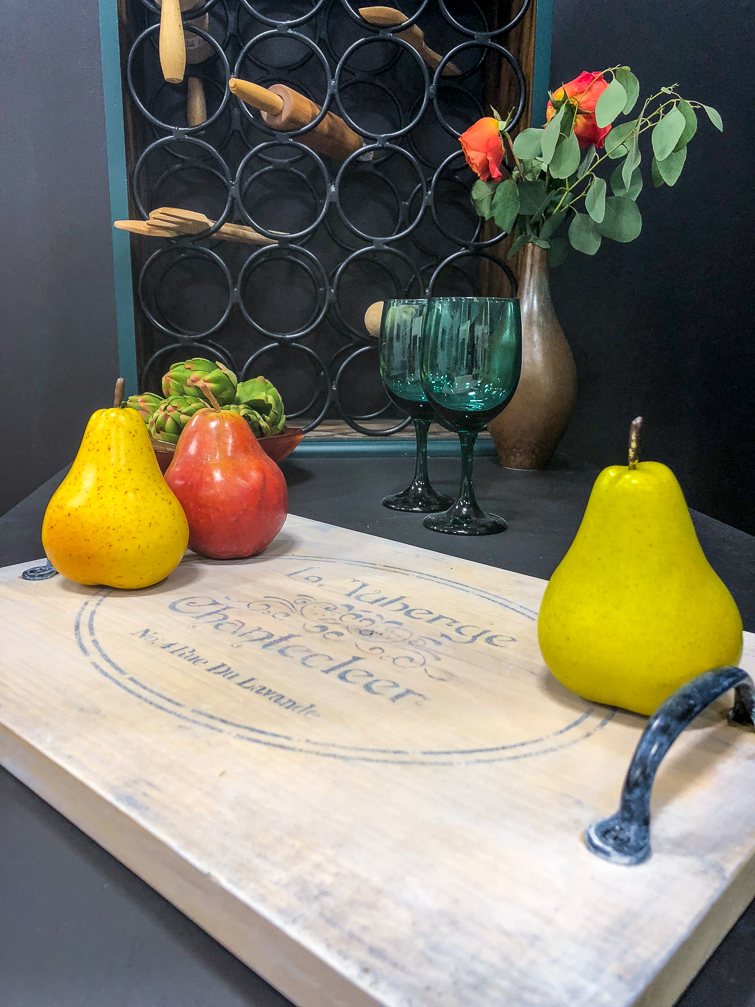 whitewashed cutting board with pears sitting on it in front of a wine rack