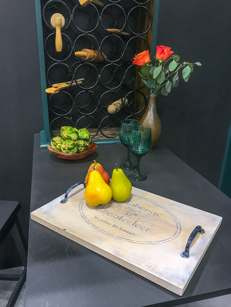 whitewashed cutting board with pears sitting on a black table wine bar